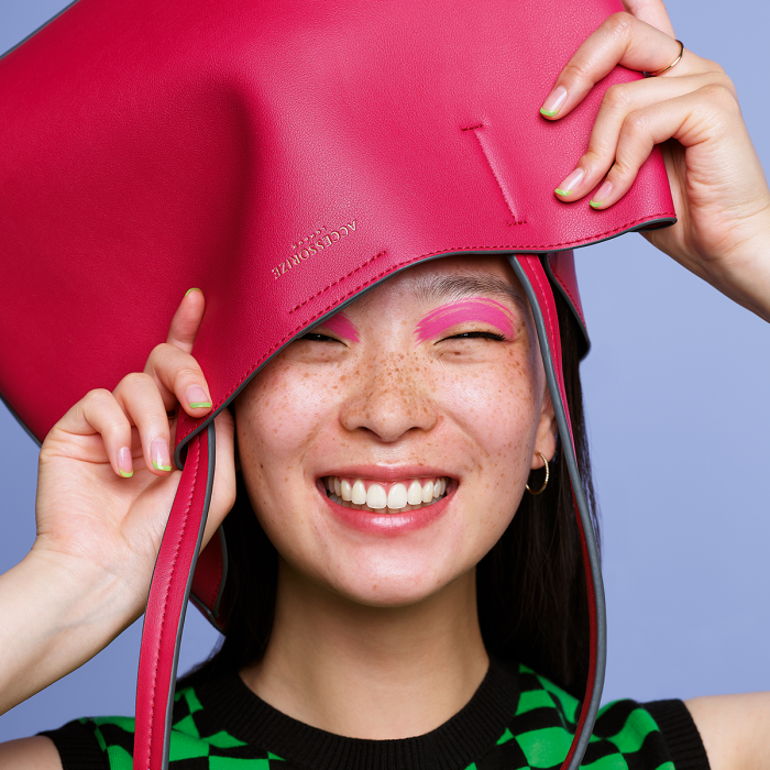 Smiling young lady with pink eye shadow holding a pink leather bag over her head