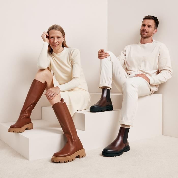 A man and woman dressed in white wearing leather boots