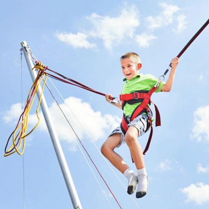 Child on a bungee trampoline against a blue summer sky