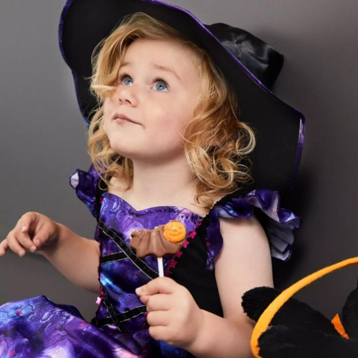 Child holding a lollipop wearing a black and purple witch costume