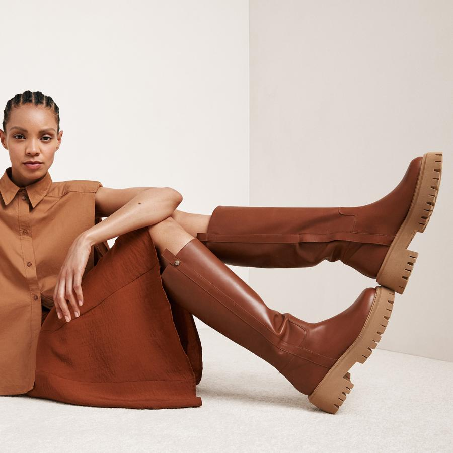 Model in brown is showing off a pair of long brown chunky leather boots