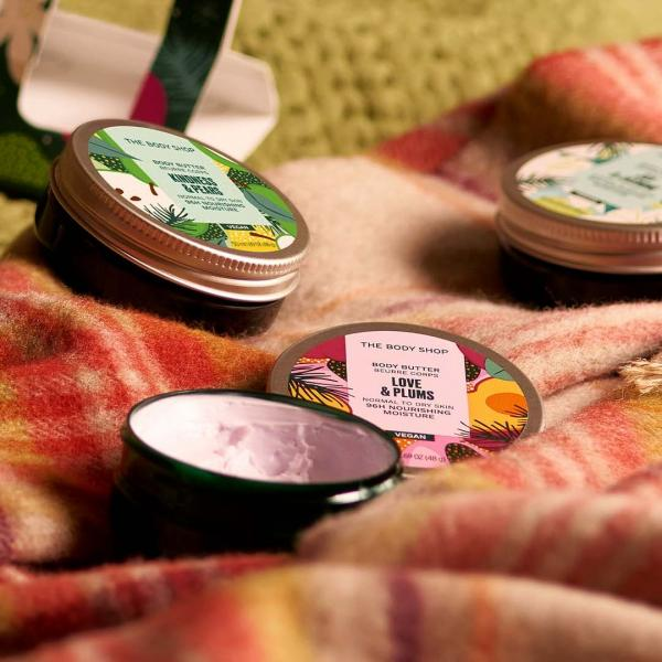 Tubs of body butter on a tartan rug